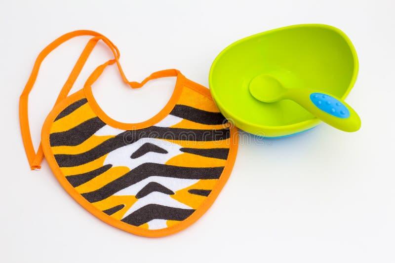 Bavoir, cuvette et cuillère pour le bébé photos libres de droits