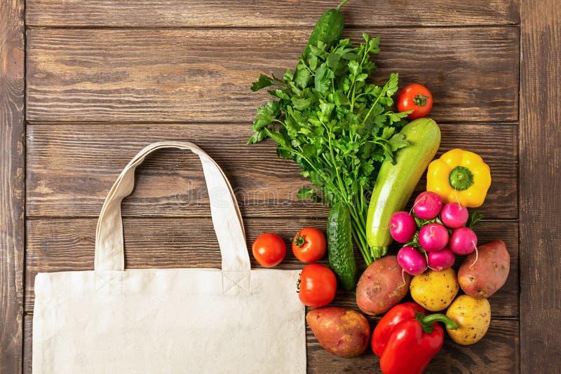 Bawe?niana torba na zakupy i ?wiezi nieociosani warzywa na drewnianym tle poj?cia eco pokoju go??bie kosmos kopii P?aski uk?ad zdjęcia stock
