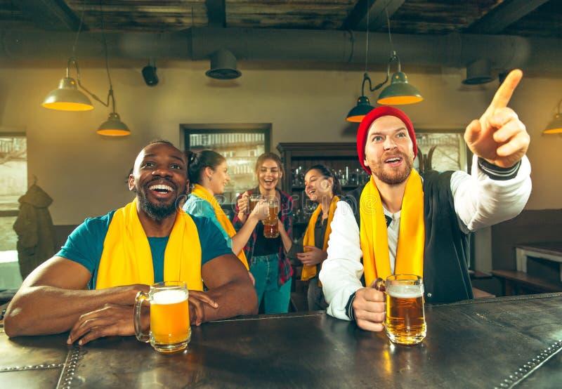 Bawi się, zaludnia, czasu wolnego, przyjaźni i rozrywki pojęcie, szczęśliwi fan piłki nożnej lub męscy przyjaciele pije piwo - i obrazy stock