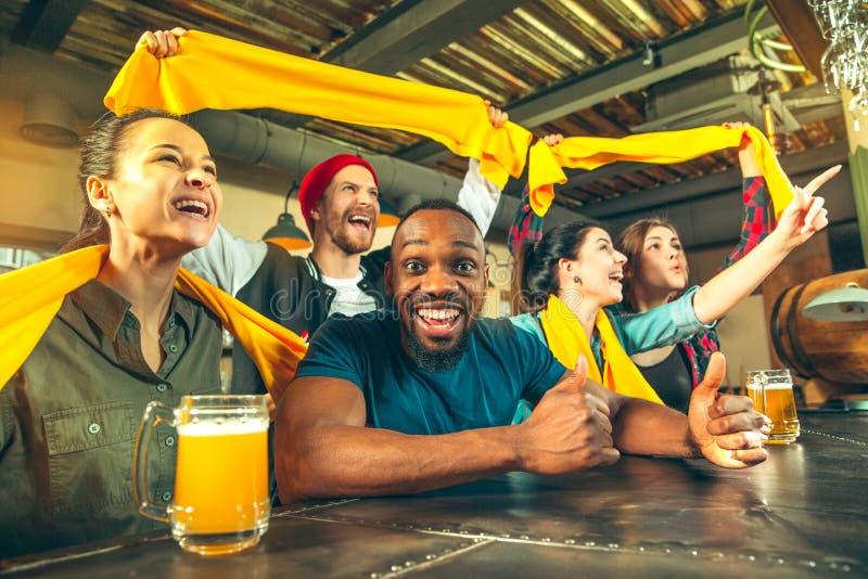 Bawi się, zaludnia, czasu wolnego, przyjaźni i rozrywki pojęcie, szczęśliwi fan piłki nożnej lub męscy przyjaciele pije piwo - i obraz stock