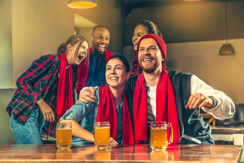 Bawi się, zaludnia, czasu wolnego, przyjaźni i rozrywki pojęcie, szczęśliwi fan piłki nożnej lub męscy przyjaciele pije piwo - i zdjęcie stock