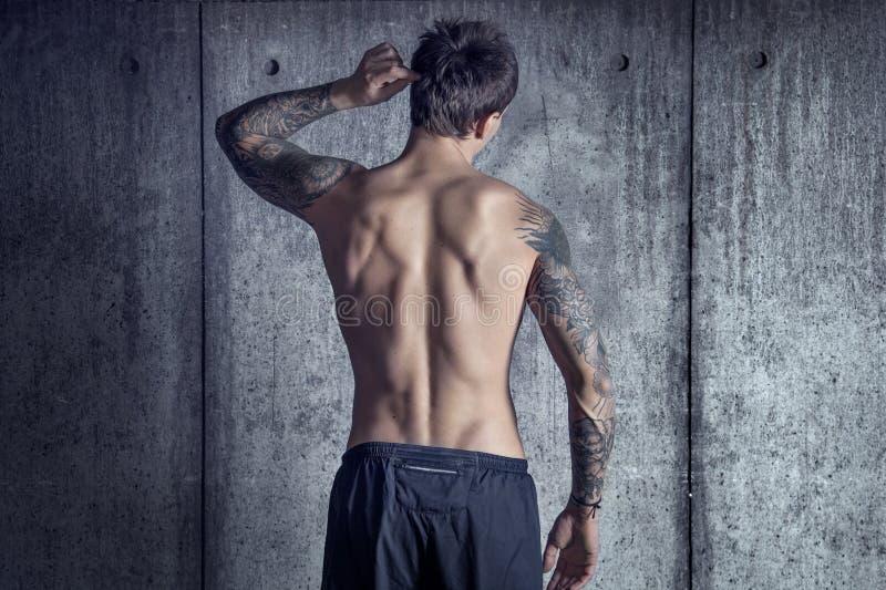 Bawi się dysponowanego mięśniowego tatuującego faceta od plecy w loft przestrzeni fotografia royalty free