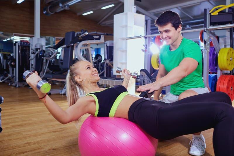 Bawi się dziewczyny robi brzusznym ćwiczeniom z osobistym trenerem przy obrazy stock