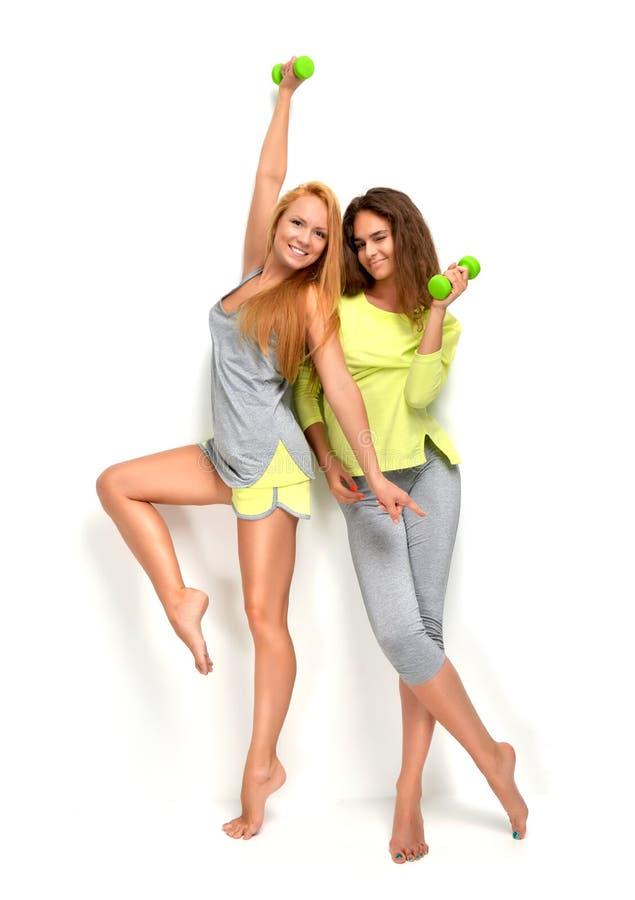 Bawi się kobiety uśmiechniętego roześmianego przytulenie z zielonym sprawności fizycznej dumpbel fotografia royalty free