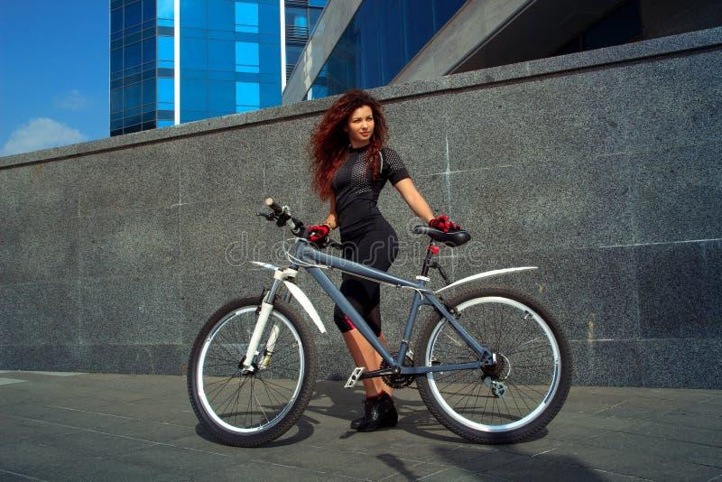 Bawi się kobiety z kędzierzawym czerwonym włosy na bicyklu obrazy stock