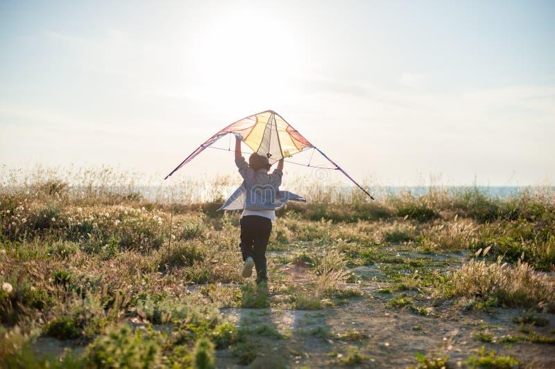 Bawi się małego dziecka biega w kierunku lato dennego horyzontu z kanią w jego rękach fotografia stock