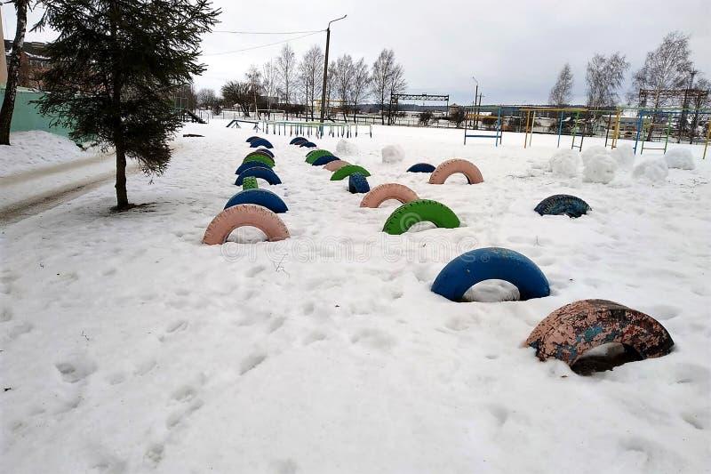 Bawi się na otwartej przestrzeni, przeszkoda kurs na boisku szkolnym, barwiący ciężarowi koła, radośnie, zima, zdjęcia stock
