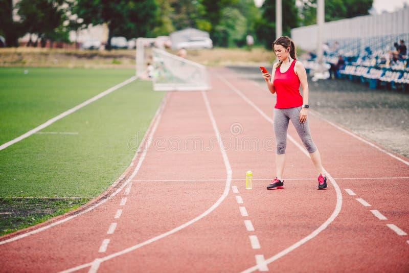 Bawi się sprawności fizycznych Kaukaskie kobiety robi rozgrzewce przed ćwiczeniem Atlety rozciągania nogi robi rozgrzewce przed t zdjęcie royalty free
