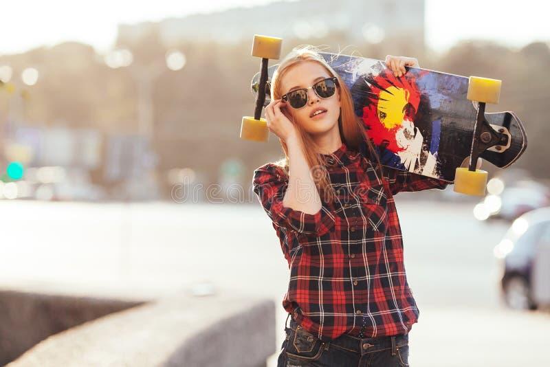 Bawi się szczęśliwej dziewczyny pozuje w lecie z deskorolka Elegancka szczęsliwa modniś kobieta z kolorowym longboard w zmierzchu zdjęcie stock