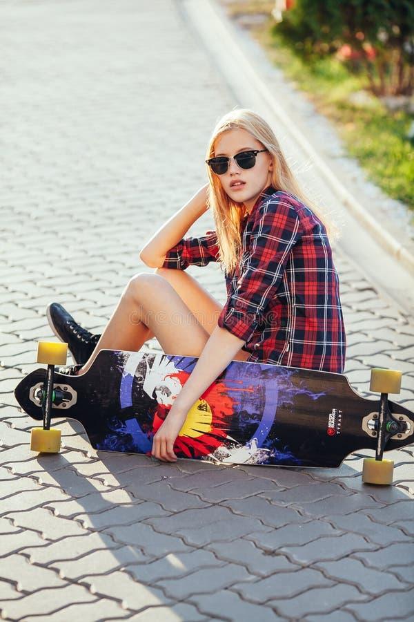 Bawi się szczęśliwej dziewczyny pozuje w lecie z deskorolka Elegancka szczęsliwa modniś kobieta z kolorowym longboard w zmierzchu obraz royalty free