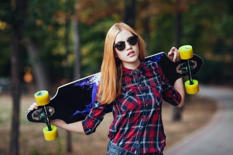 Bawi się szczęśliwej dziewczyny pozuje w lecie z deskorolka Elegancka szczęsliwa modniś kobieta z kolorowym longboard w zmierzchu obrazy stock