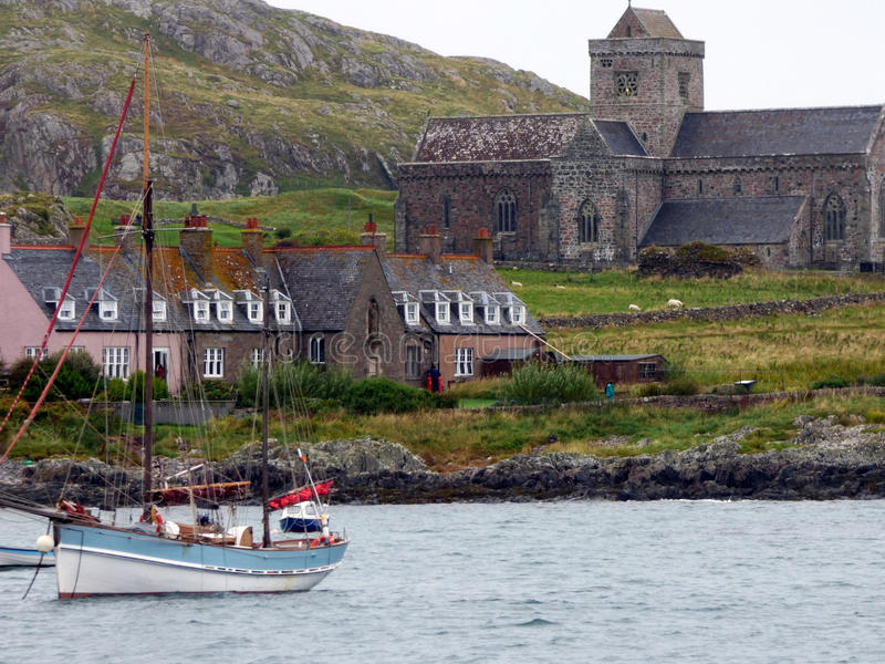 The Bay, the Benedictine Abbey of Iona and Bishops House, Isle of Iona, Scot. A view of the Abbey of Iona and the rear of Bishops House, with a sailing boat in royalty free stock photography