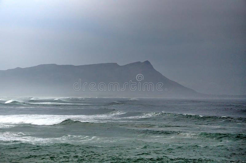 Bay in Kleinmond, South Africa. Kleinmond, South Africa, shrouded in mist, with a mountain in the background stock images