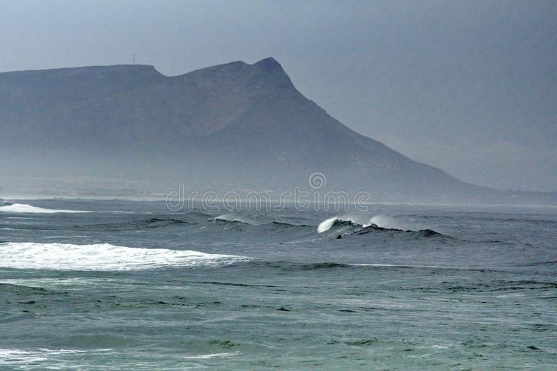 Bay in Kleinmond, South Africa. Kleinmond, South Africa, shrouded in mist, with a mountain in the background stock photography