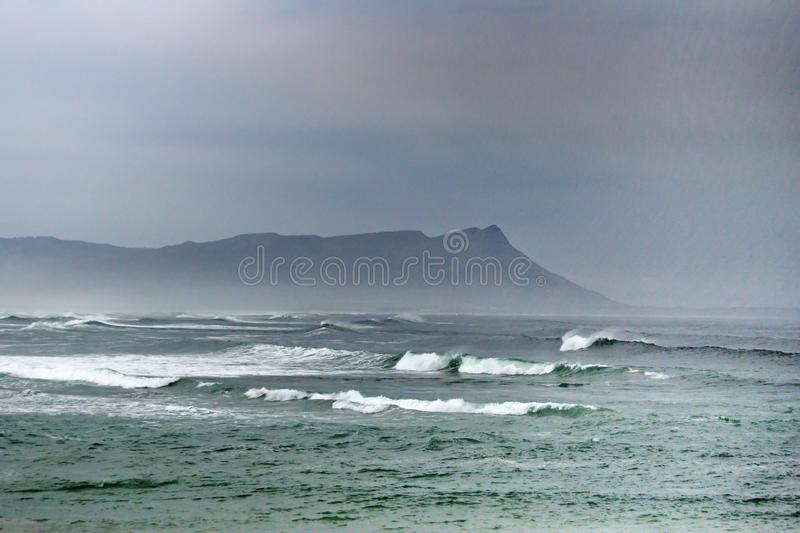 Bay in Kleinmond, South Africa. Kleinmond, South Africa, shrouded in mist, with a mountain in the background royalty free stock photo