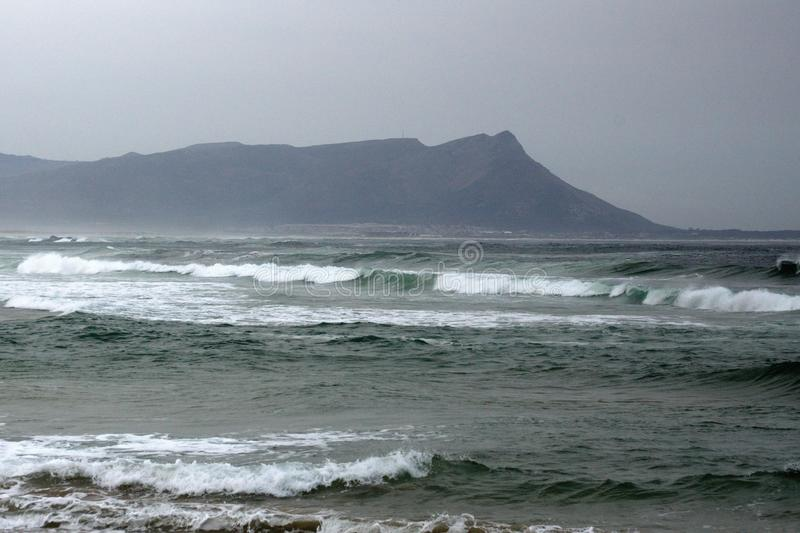 Bay in Kleinmond, South Africa. Stormy seas off the coast of Kleinmond, South Africa, with a mountain in the background stock photos