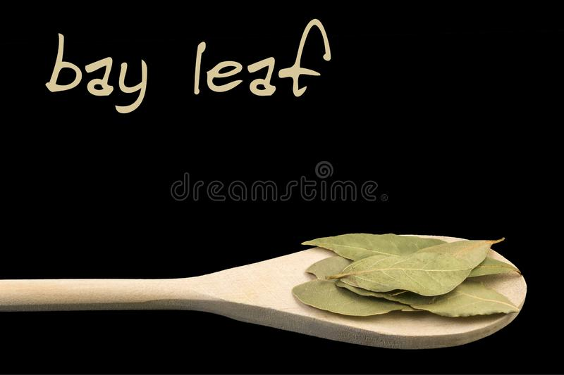 Bay leaf on wooden spoon isolated on black background. Latin name Laurus nobilis stock image