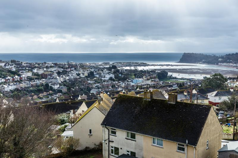 The bay near the city. Cloudy day, view from top to city by the sea; the bay near the city, seen at low tide; Teignmouth, United Kingdom royalty free stock photography