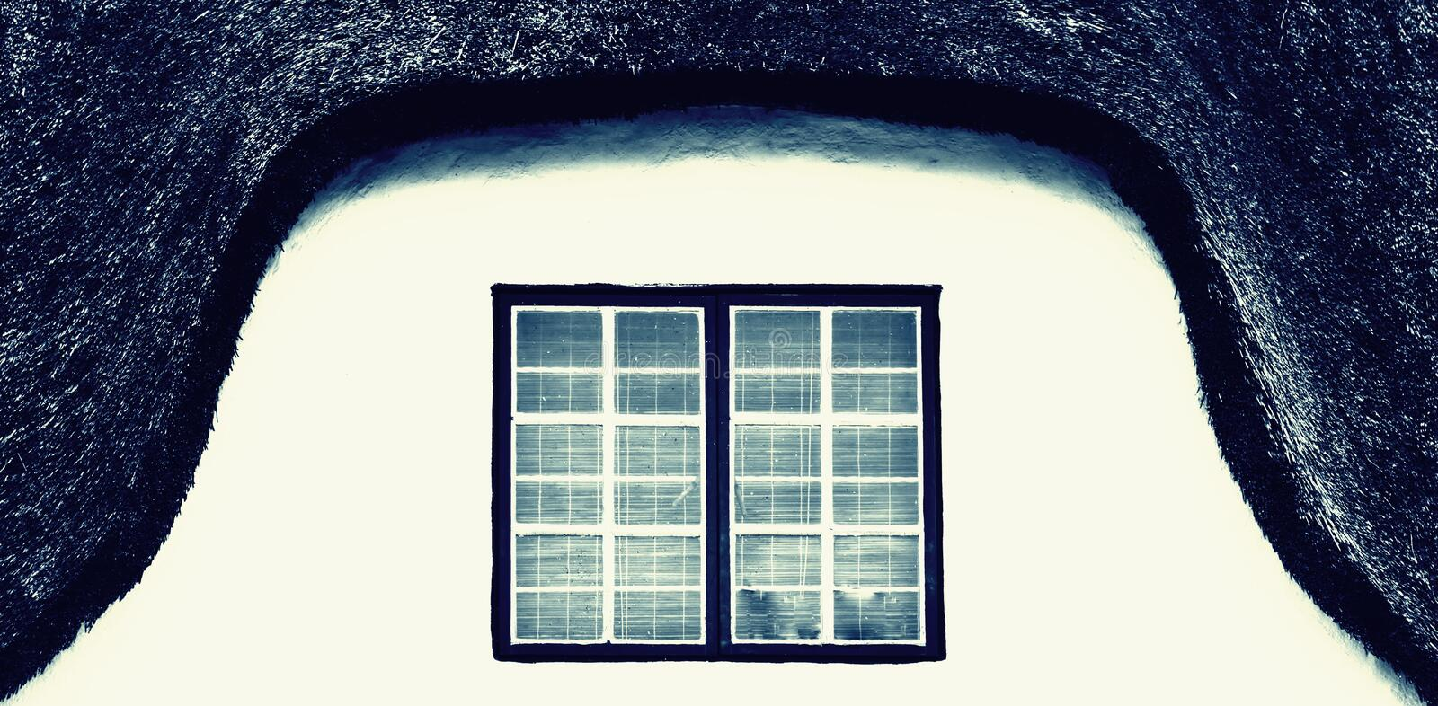 Bay window on a thatch roof house. Close up of a bay window on a thatch roof house royalty free stock images