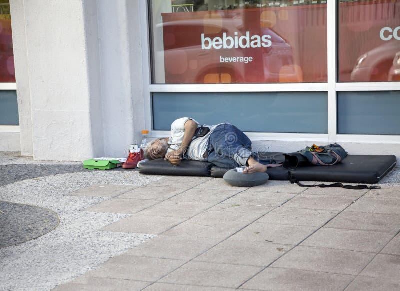 Man who pan handles sleep on street in Bayamon Puerto Rico. BAYAMON, PUERTO RICO/USA - February 10, 2019: Pan handling man sleeps on a mat on the sidewalk royalty free stock photography