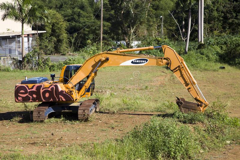 Parked heavy construction excavator with graffitii on grass Bayamon Puerto Rico. BAYAMON, PUERTO RICO/USA - February 9, 2019: Parked heavy construction excavator royalty free stock photo