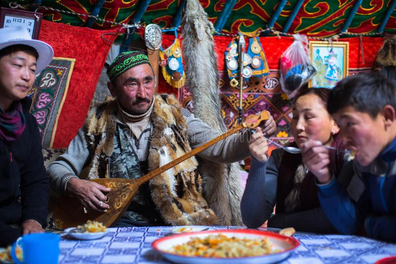 Kazakh family of hunters with hunting birds golden eagles inside the mongolian Yurt. BAYAN-OLGII, MONGOLIA - SEP 28, 2017: Kazakh family of hunters with hunting stock photos