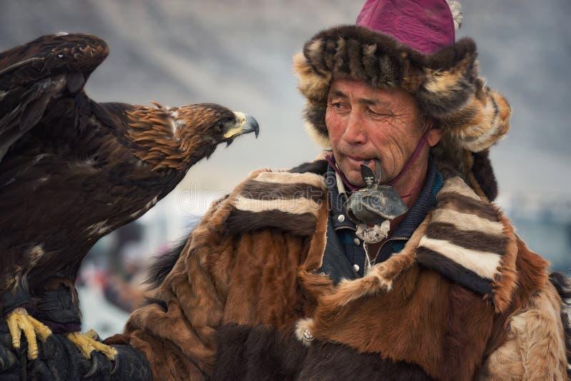 Bayan-Olgii Mongoliet - Oktober 01, 2017: Festival av jägare med Golden Eagles Stående av obekanta mongoliska Hunter With Ber arkivbilder