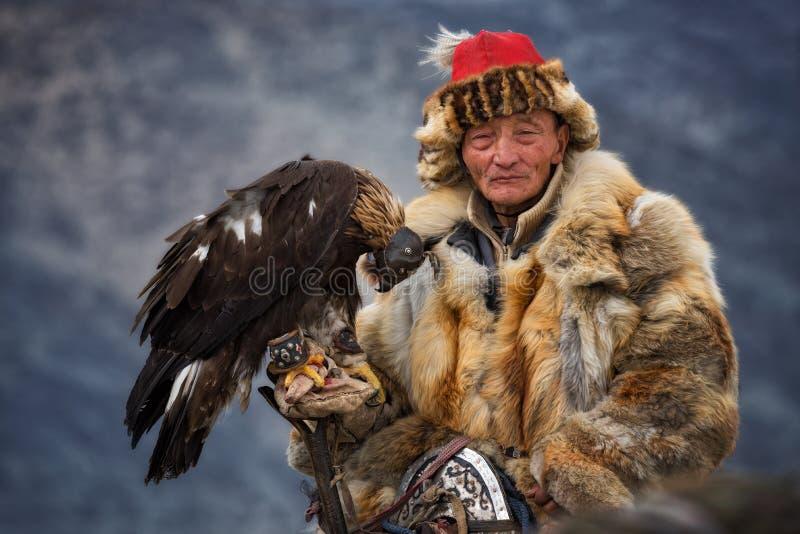 Bayan-Olgii Mongoliet - Oktober 01, 2017: Guld- Eagle Festifal Gammal pittoresk mongolisk Hunter In Traditional Clothes Of rävpäl arkivfoto
