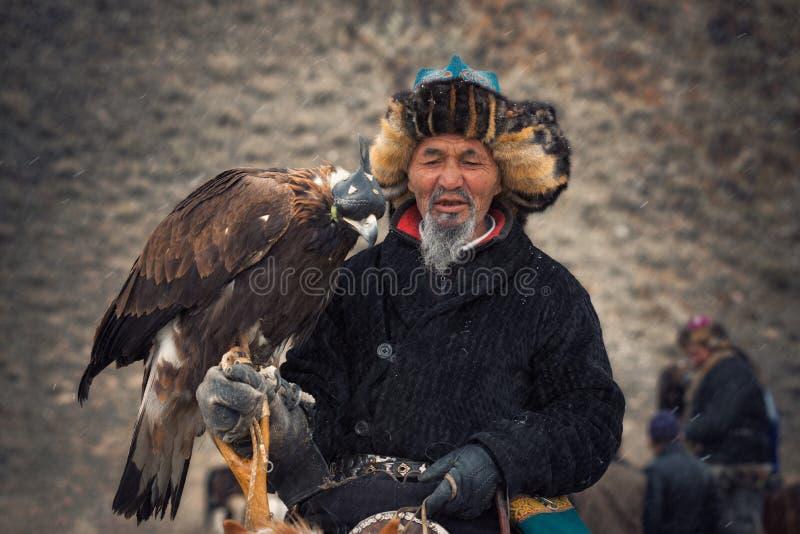Bayan-Olgii Mongoliet - Oktober 01, 2017: Guld- Eagle Festifal Stående av pittoreska gamla Greybearded mongoliska Hunter Berkutch royaltyfria foton