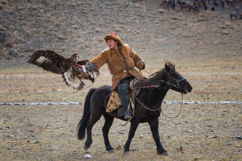 Bayan-Ulgii, Монголия - 1-ое октября 2017: Фестиваль беркута Неизвестный монгольский охотник так называемое Berkutchi Astride на  стоковые фотографии rf