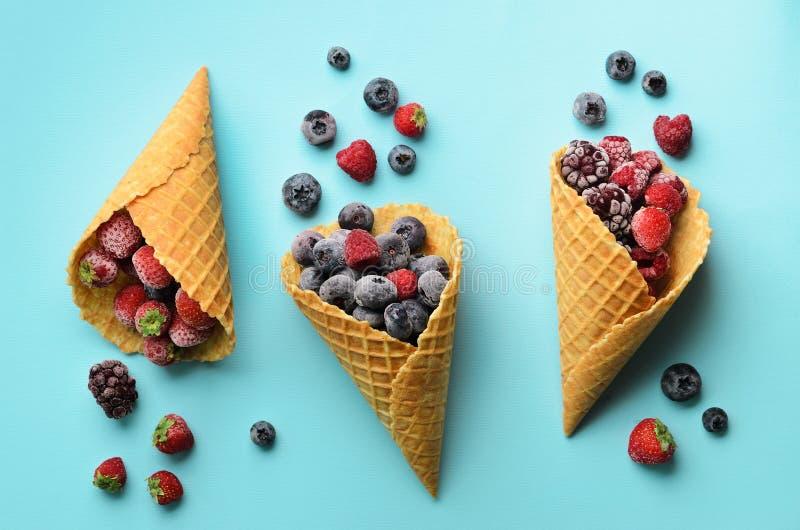 Bayas congeladas - fresa, arándano, zarzamora, frambuesa en conos de la galleta en fondo azul Visión superior bandera foto de archivo