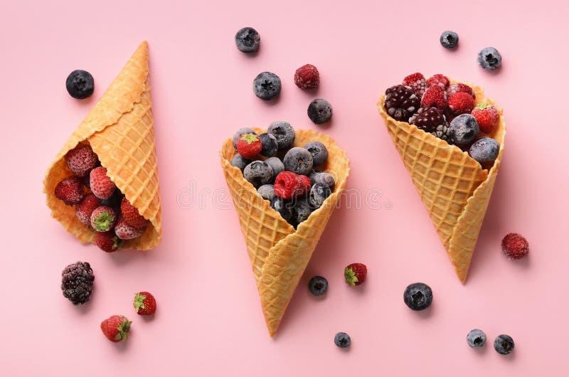 Bayas congeladas - fresa, arándano, zarzamora, frambuesa en conos de la galleta en fondo rosado Visión superior bandera fotografía de archivo libre de regalías