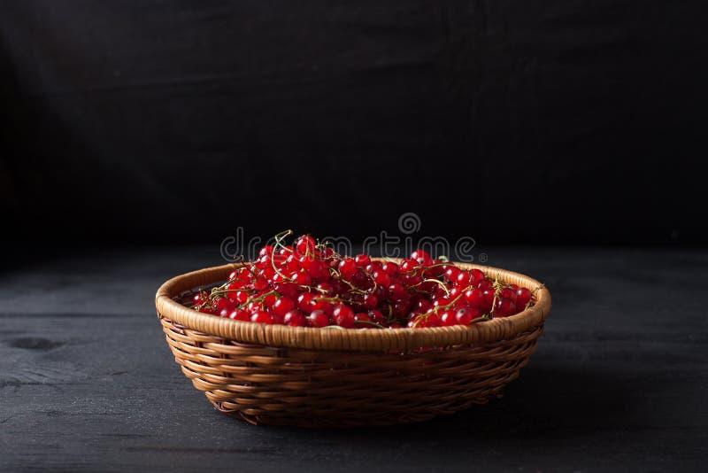 Bayas de la pasa roja en una cesta en un fondo negro imagen de archivo