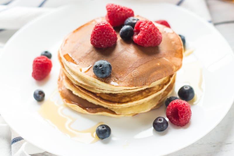 Bayas del desayuno Crepes Desayuno romántico en una tabla de madera Campo de la mañana del resorte? de la hierba verde y del ciel fotografía de archivo