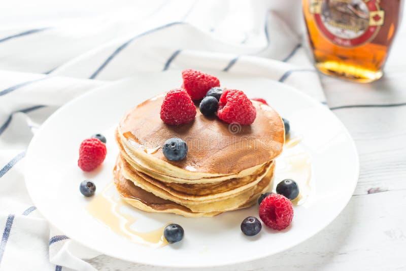 Bayas del desayuno Crepes Desayuno romántico en una tabla de madera Campo de la mañana del resorte? de la hierba verde y del ciel foto de archivo libre de regalías