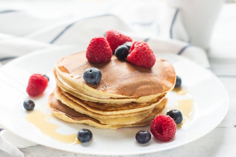 Bayas del desayuno Crepes Desayuno romántico en una tabla de madera Campo de la mañana del resorte? de la hierba verde y del ciel imagen de archivo libre de regalías