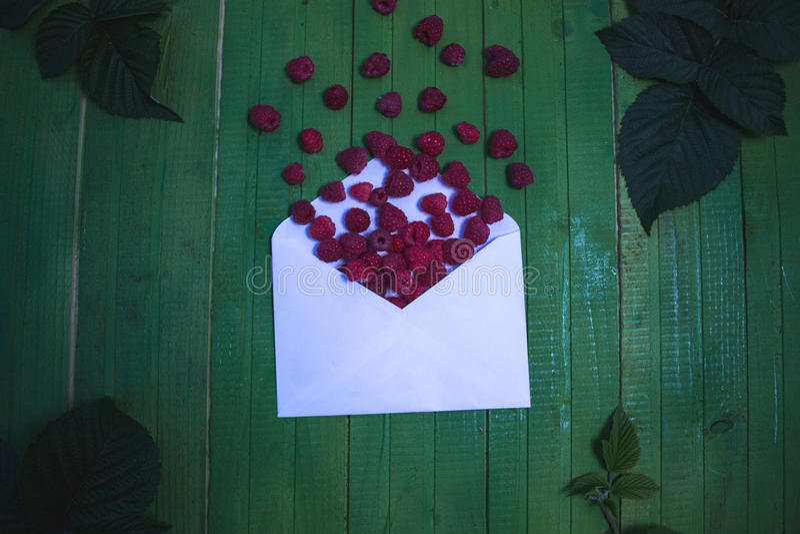 Bayas frescas de la frambuesa en un sobre en un fondo de madera verde imagen de archivo libre de regalías
