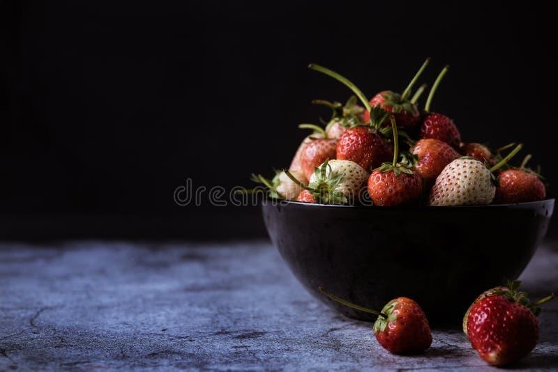 Bayas frescas de la fresa en un cuenco de negro fotografía de archivo libre de regalías