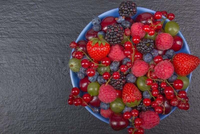 Bayas frescas del diverso verano en un cuenco en la tabla de madera rústica Antioxidantes, dieta del detox, frutas orgánicas Visi fotografía de archivo libre de regalías