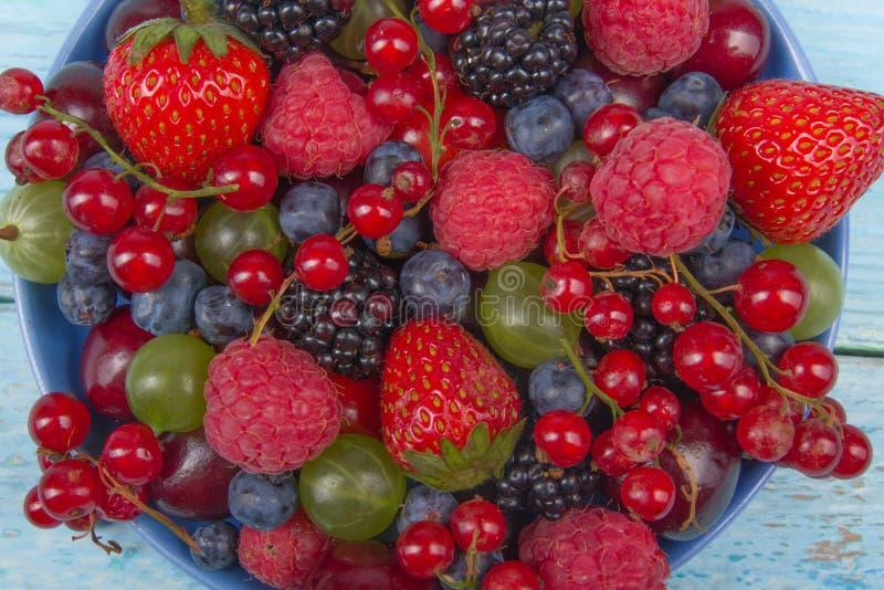Bayas frescas del diverso verano en un cuenco en la tabla de madera rústica Antioxidantes, dieta del detox, frutas orgánicas Visi foto de archivo