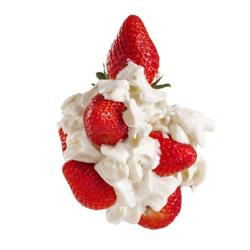 Bayas frescas rojas de la fresa en el primer blanco de la crema de la leche aislado en el fondo blanco foto de archivo