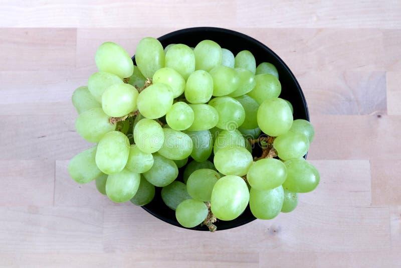 Bayas verdes maduras de la uva en la opinión superior del cuenco redondo negro imágenes de archivo libres de regalías