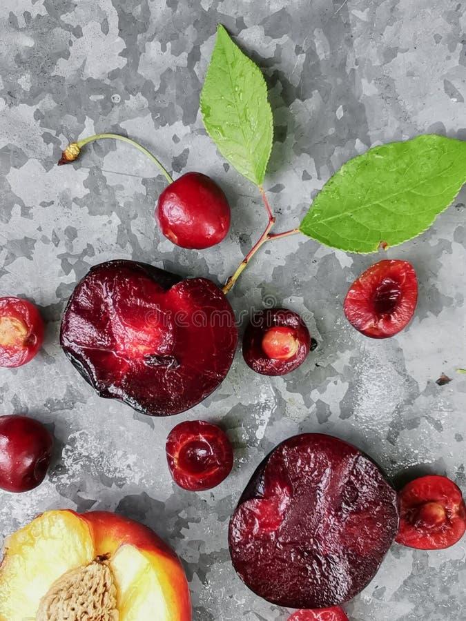 Bayas y frutas maduras frescas del verano, melocotones, albaricoques, cereza y ciruelo en una placa redonda en la tabla imagen de archivo
