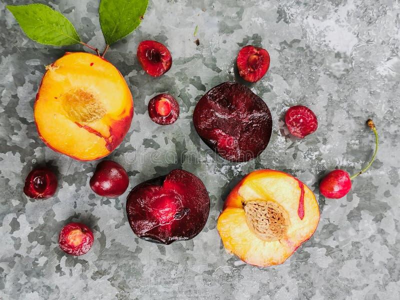 Bayas y frutas maduras frescas del verano, melocotones, albaricoques, cereza y ciruelo en una placa redonda en la tabla foto de archivo