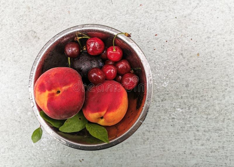 Bayas y frutas maduras frescas del verano, melocotones, albaricoques, cereza y fresa en una placa redonda imágenes de archivo libres de regalías