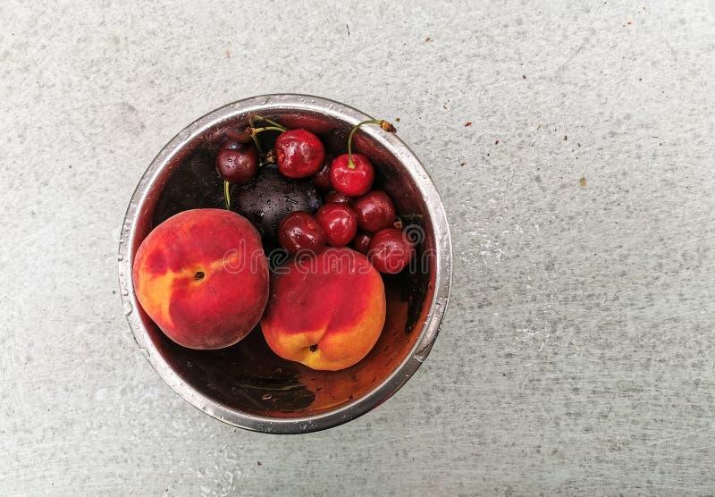 Bayas y frutas maduras frescas del verano, melocotones, albaricoques, cereza y fresa en una placa redonda foto de archivo