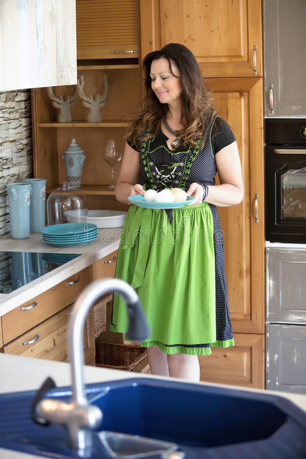 Bayerische Frau, die in der Küche hält eine Platte steht stockfotografie