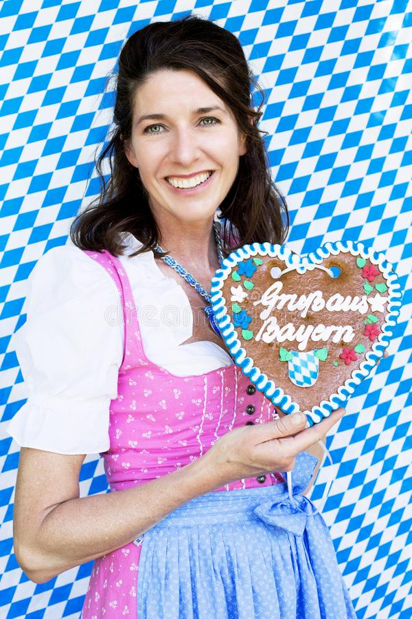 Bayerische Frau im Dirndl, der einen Herz-förmigen Lebkuchen hält stockbilder