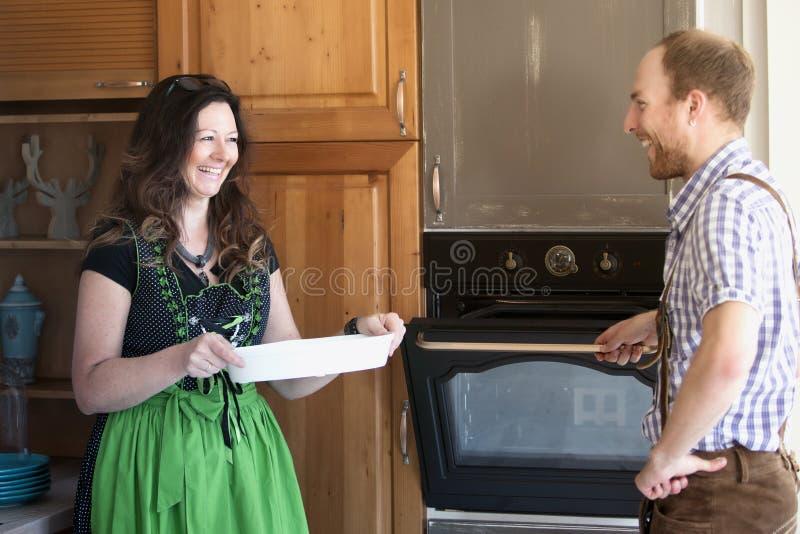 Bayerische Paare, die am Ofen in der Küche stehen lizenzfreies stockbild