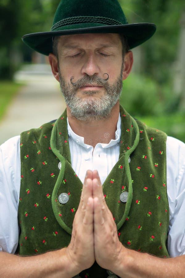 Bayerischer draußen stehender und betender Mann lizenzfreie stockfotos